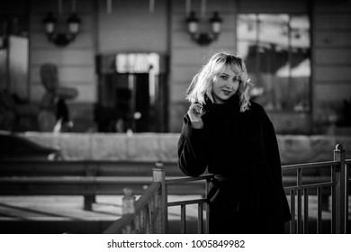 A pleasant smiling woman, citizen walks in a city with a good mood. Lifestyle of the inhabitants of the big city, their joy and sorrow. Walking on a fresh spring day and distraction from problems