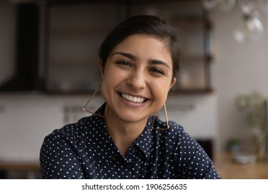 Pleasant smiling young indian woman freelancer looking at camera consult client from computer phone screen via video call. Headshot portrait of mixed race lady taking part in web conference from home