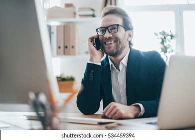 Pleasant talk with business partner. Portrait of handsome man in eyeglasses talking on the phone and smiling while sitting on working place in creative office
