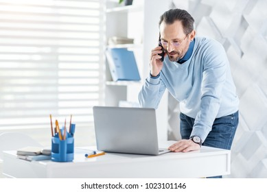 Pleasant talk. Handsome alert dark-haired bearded man talking on his phone and looking at the screen of his laptop while standing near the table