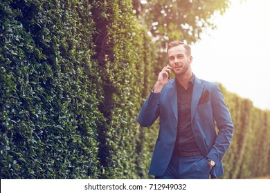 Pleasant talk. Low angle of a positive handsome businessman talking on smart phone and enjoying the talk while walking in the garden