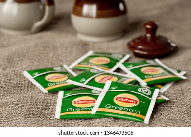Pleasant Valley, Canada - March 22, 2019: Lipton green tea packets on burlap. Lipton is named after it's founder Thomas Lipton and is owned by Unilever.