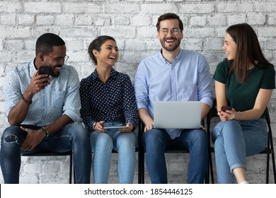Pleasant waiting. Group of four multiethnic millennial men and women teammates friends spending time in queue at wifi zone talking laughing sharing information by internet app using electronic devices