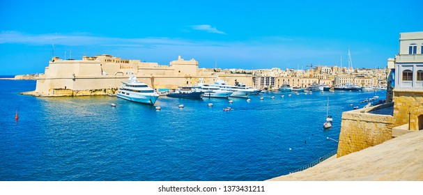 The pleasant walk in upper town of Senglea with a view on Vittoriosa marina, luxury yachts at Birgu shore and medieval Fort St Angelo, Malta.