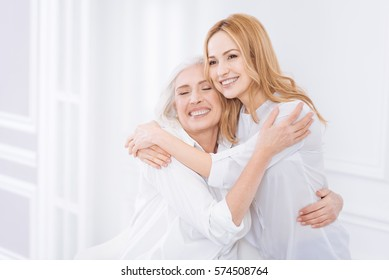 Pleasant woman and her mother embracing