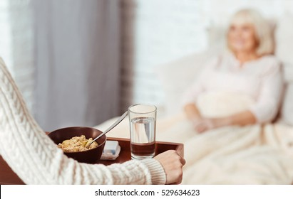 Pleasant woman holding tray with breakfast