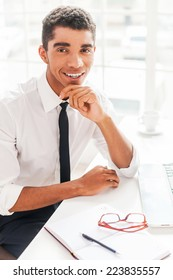 Pleasant working! Handsome young Afro-American man in shirt and tie holding hands on chin and smiling while sitting at his working place