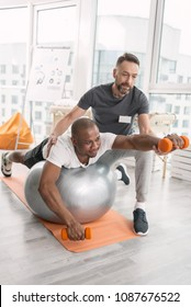 Pleasant workout. Joyful nice positive man smiling while enjoying the physical training
