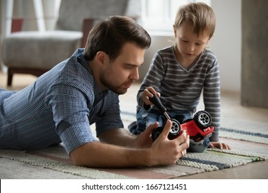 Pleasant young father lying on floor carpet, imagining repairing car with focused little kid son. Small child boy holding screwdriver, fixing broken toy with controlling dad, skills transmission.