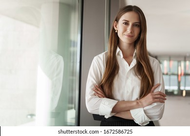 Pleasant young female assistant, manager standing in office corridor near window, with pleased confident expression, cross hands over chest showing readiness, business and women concept