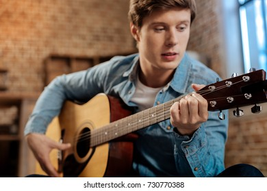 Pleasant young man playing guitar at home