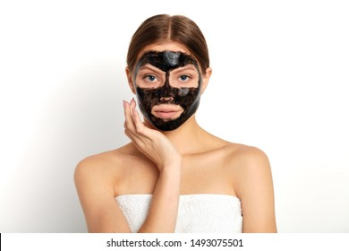 pleasant young woman applying a mask on her face, close up portrait, isolated white background, studio shot,