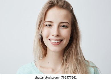 Pleasant-looking woman with dark eyes, beautiful lips and pure skin looking with smile at camera rejoicing her vacation, relaxing. Positive female with long blonde hair posing against gray wall