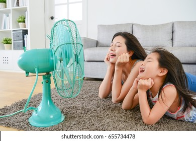 pleasantly mother with young little daughter lying down on living room floor and face to electric fan enjoying blowing cool wind together at summer.