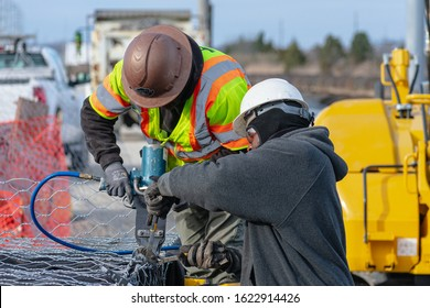 Pleasantville, NJ / USA - November 27, 2019: Two men constructing a gabion wall for the creation of a service road near East Delilah Road.