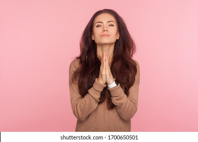 Please, I beg you! Portrait of worried young woman with brunette wavy hair praying for help, expressing big hope with imploring pleading eyes, appealing to forgive. indoor studio shot, pink background
