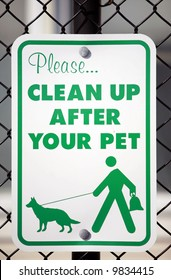 """a """"please clean up after your pet"""" sign in a park"""