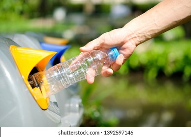 Please dispose of plastic bottle into the tank. A man throw rubbish in the trash can by separate garbage to dispose like hazardous waste ,