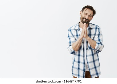 Please do me favor for last time. Portrait of nervous and miserable man suffering from alcohol addiction, frowning and making sad face while holding hands in pray and begging friend