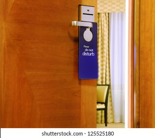 Please do not disturb sign hanging on open door in a hotel
