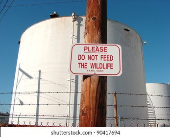 please do not feed wildlife sign with industrial tank in background