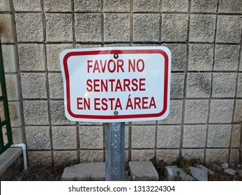 please don't sit in this area sign in Spanish with wall