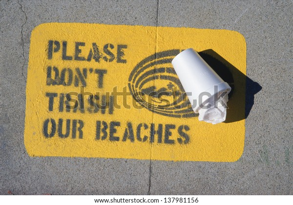 `Please don't trash our beaches` sign on a pavement