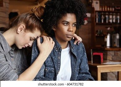 Please forgive me. Mad angry black woman dressed in denim jacket pouting, ignoring apologies of her white redhead female partner who hugging her and begging for forgiveness after having quarrel