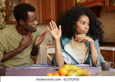 Please forgive me. Unhappy African American male cheater holding hand on his chest apologizing to beautiful indifferent woman who ignoring and refusing all his excuses, telling him to get lost