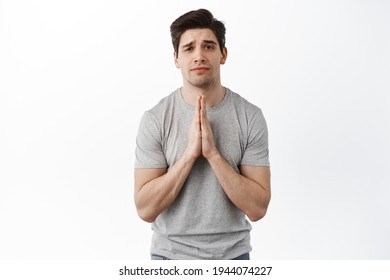 Please help. Coy man begging for favour, need something, pleading you with desperate gloomy face, standing over white background