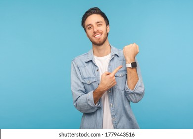Please, hurry up! Portrait of cheerful punctual man in worker denim shirt pointing at wrist watch and smiling, showing smartwatch devise with mock up display. indoor isolated on blue background