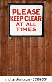 please keep clear at all times vintage sign at a wooden fence background