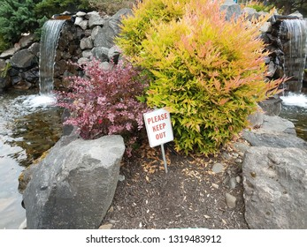 please keep out sign with rocks and waterfalls and bushes