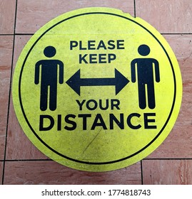 Please keep your distance bright yellow floor sign