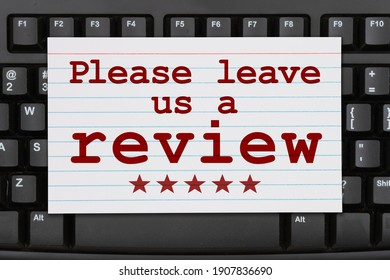 Please leave a review message on a index card on a black keyboard