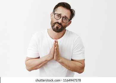 Please I need your help right now. Portrait of upset and gloomy good-looking man in desperate situation, holding hands in pray, frowning and asking favor, begging for forgiveness over grey wall