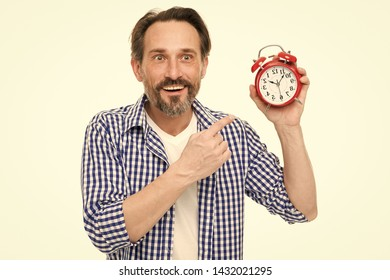 Please observe time. Mature man pointing finger at alarm clock. Mature timekeeper with analog clock. Bearded senior man with mechanical clock in hand. Timekeeping and time measurement.