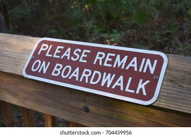 Please Remain on Boardwalk Sign