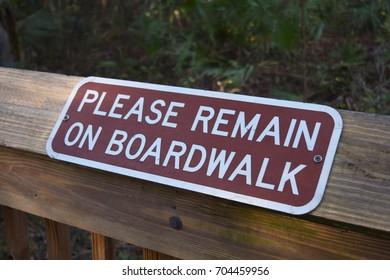 Please Remain on Boardwalk Sign