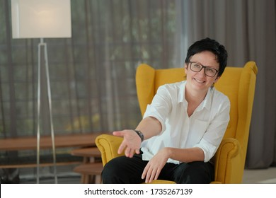 Please sit down! Woman psychologist with black hair and glasses consulting patient, psychotherapy in office.