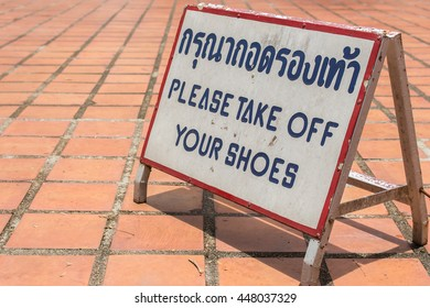 PLEASE TAKE OFF YOUR SHOES sign with Thai characters translated.