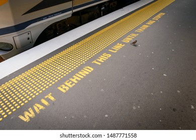 Please wait behind the line painted sign with sparrow bird (New Zealand's version of 'please mind the gap') at Wellington railway station