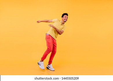 Pleased african man with sincere smile dancing on yellow background. Studio photo of enthusiastic black-haired guy wears white sneakers.