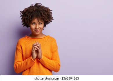 Pleased Afro American woman makes up plan, has intriguing look aside on free space, keeps palms together, looks away, wears orange jumper, isolated over purple background. People, intention concept.