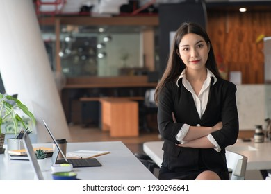 Pleased Asian businesswoman with crossed arms looking at the camera.