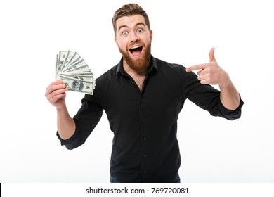Pleased bearded business man in shirt holding money and pointing on them while looking at the camera over white background
