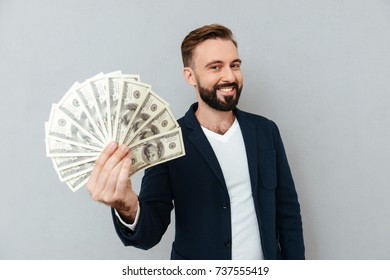Pleased bearded man in business clothes showing money and looking at the camera over gray background