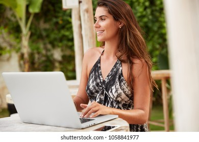 Pleased beautiful female copywriter searches information on different webpages in internet, does distnace work on laptop computer, makes presentation. People, modern technology and work concept