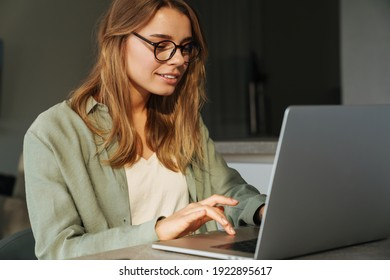 Pleased beautiful woman working with laptop while sitting at home