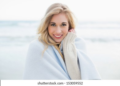 Pleased blonde woman covering herself in a blanket on the beach